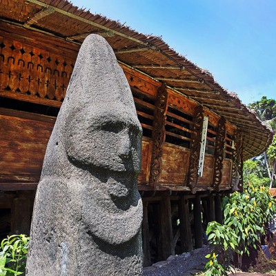 Megalith statue in front of traditional house in Dahana village, Gunungsitoli.